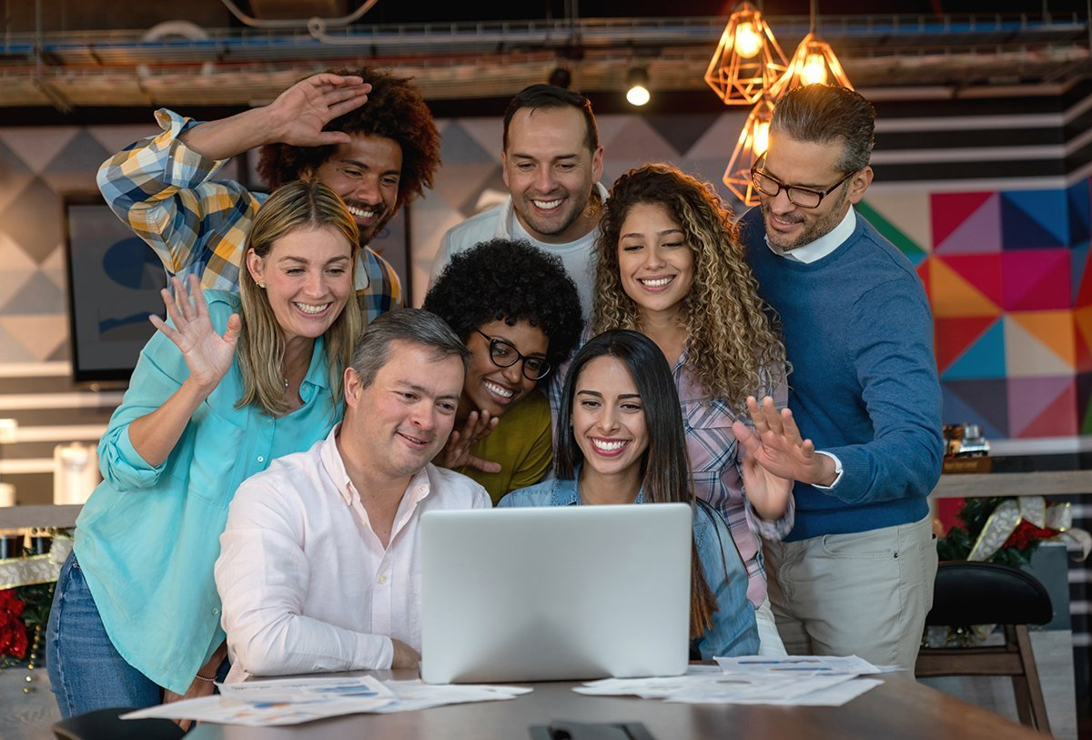 Multi ethnic young group of professionals on a video conference all saying hi looking at the screen smiling. **DESIGN ON SCREEN AND DOCUMENTS WERE MADE FROM SCRATCH BY US**